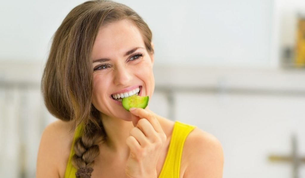 Woman eating cucumber