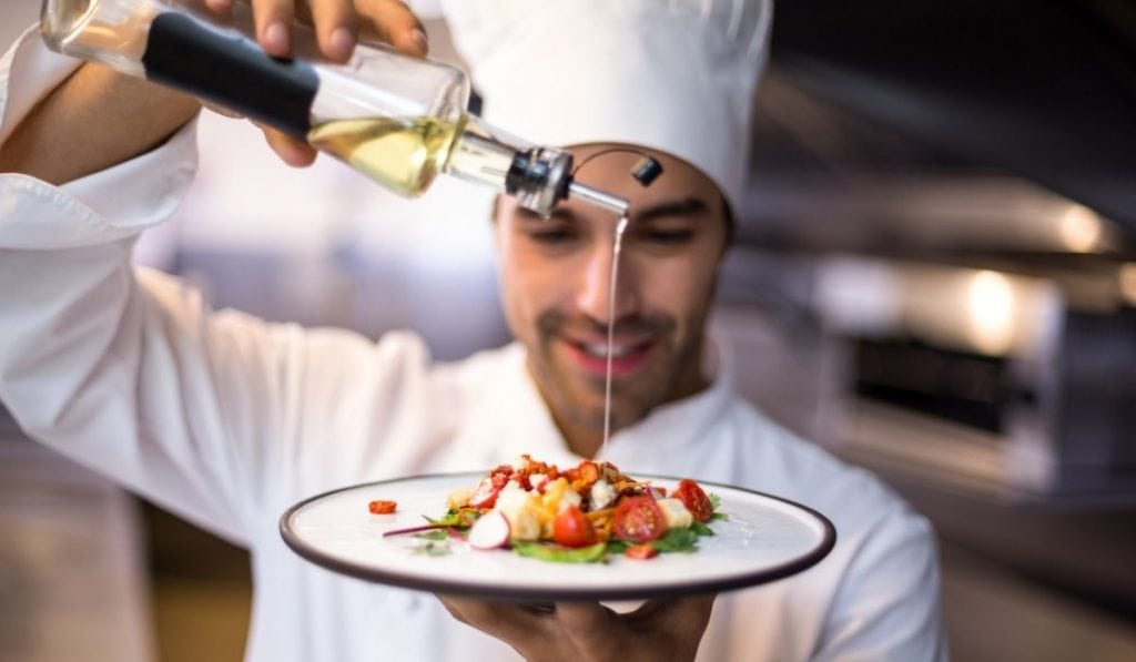 Chef Pouring Olive oil on Plate