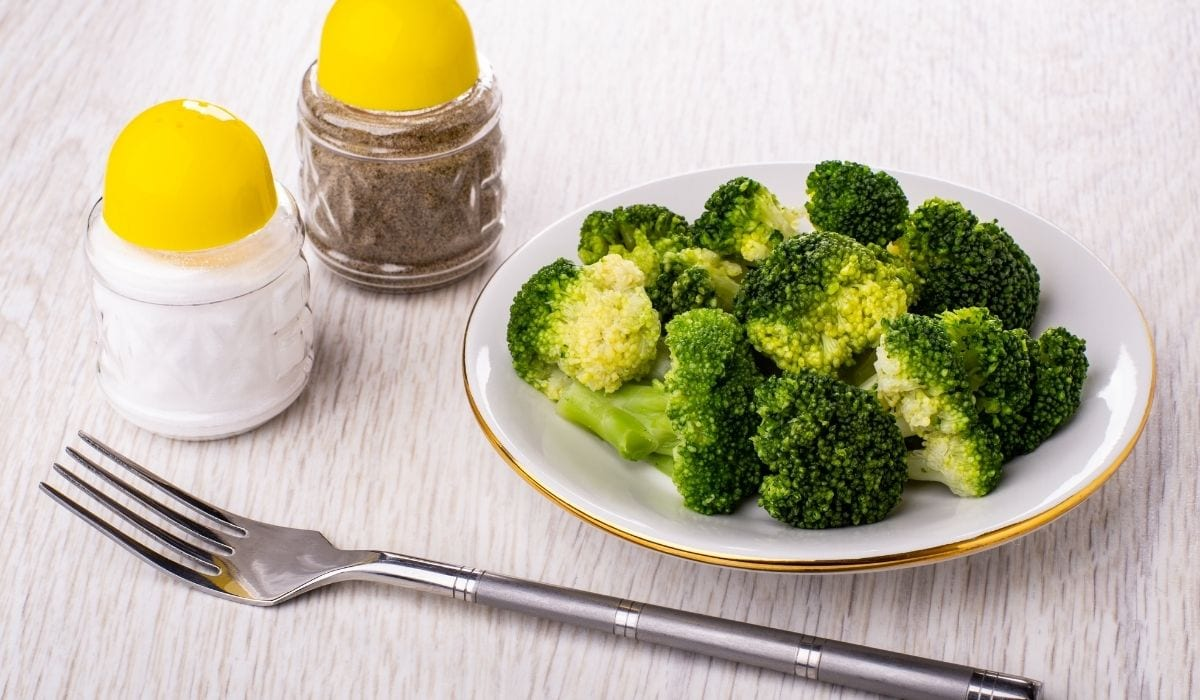 boiled broccoli in a plate with salt and pepper and fork on the table
