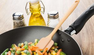frozen vegetables in a pan and bottles of oil, salt and pepper beside it