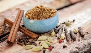 garam-masala-in-a-light-blue-bowl-on-top-of-a-wooden-table-with-cinnamon-bark-and-other-spices-surrounding-the-bowl